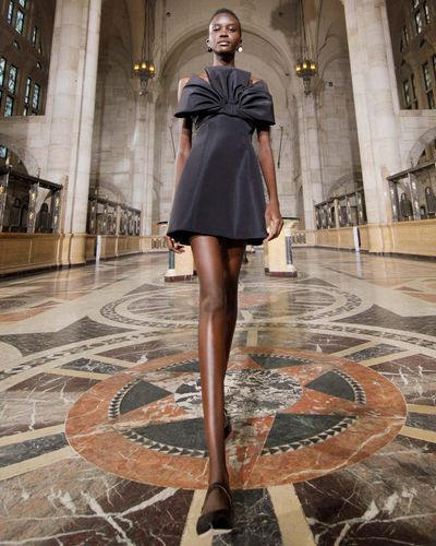 model in spring 2021 fashion show wearing little black dress with bow in a cathedral