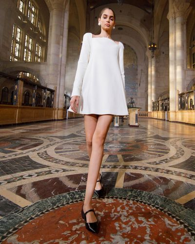 model wearing short white dress with rounded neck
