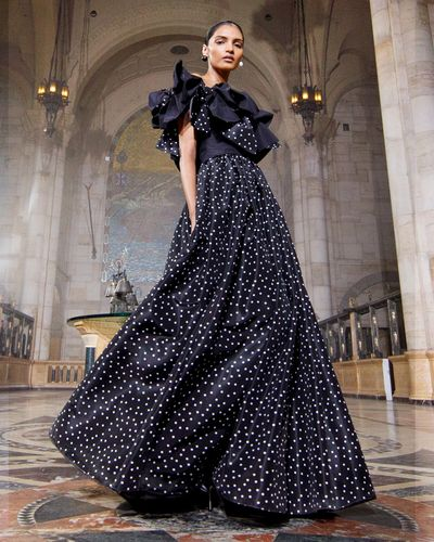 model wearing long polka dot black gown