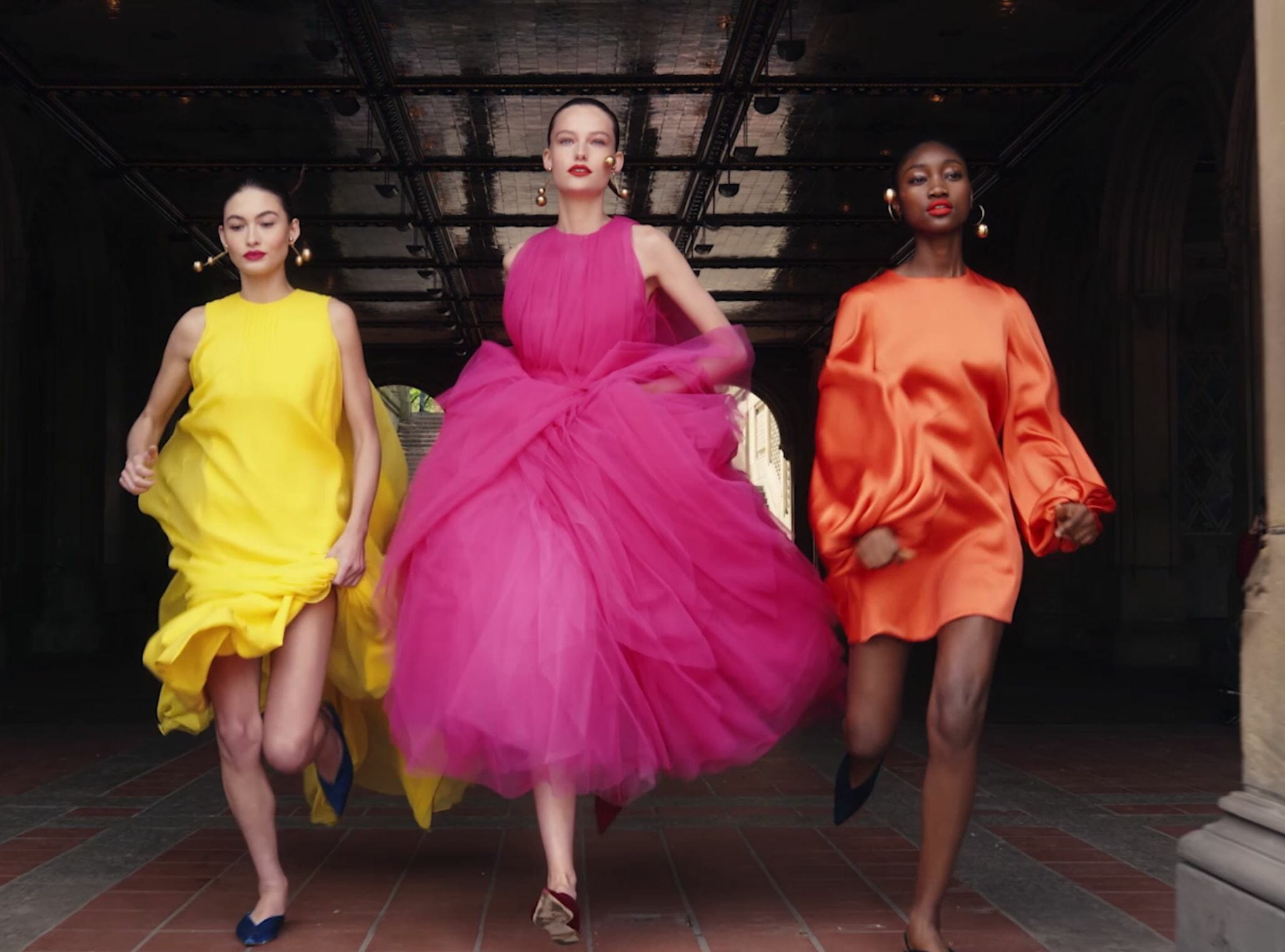 carolina herrera new york models wearing pink orange and yellow gowns running in central park